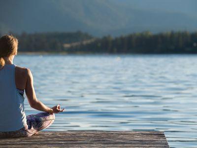 Woman by lake meditating
